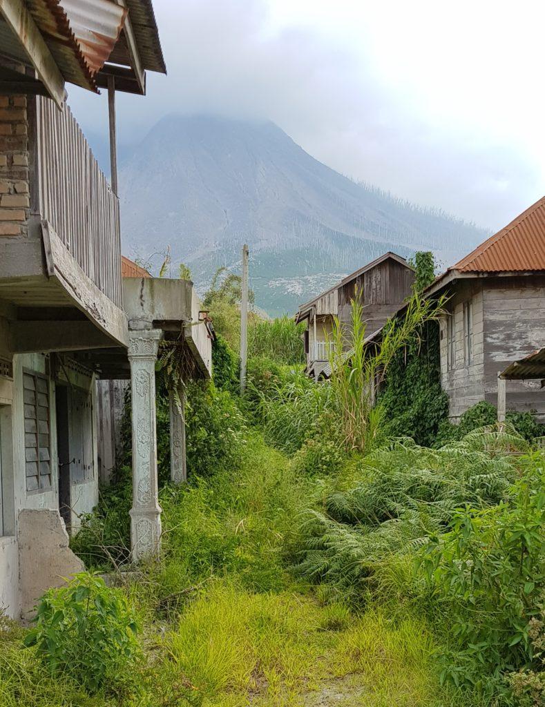 Blick durch das Geisterdorf bis zum Gunung Sinabung